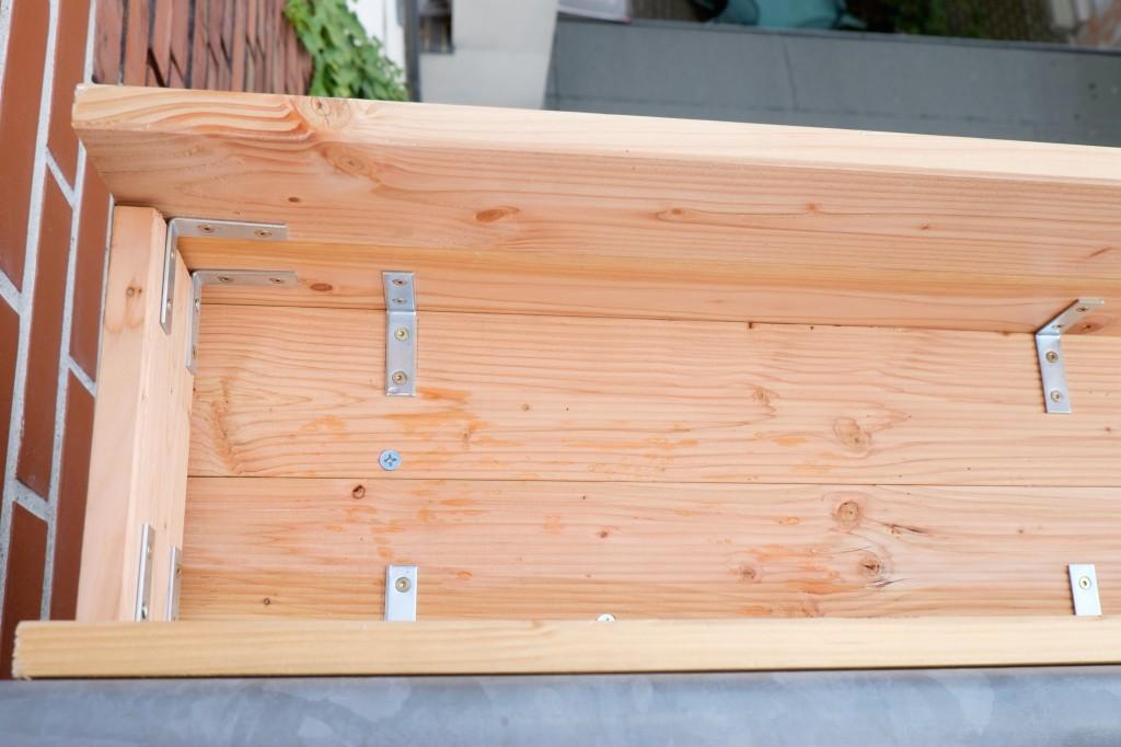 Die Winkel verbinden die Seitenteile miteinander. Die großen Schrauben gehen durch den Boden und befestigen den Kasten am Balkon.